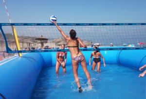 Jugadora de watervolley profesional tocando un balón encima de la red y dos defensoras esperando
