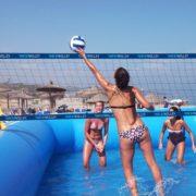 Jugadora de watervolley profesional tocando un balon encima de la red y dos defensoras esperando