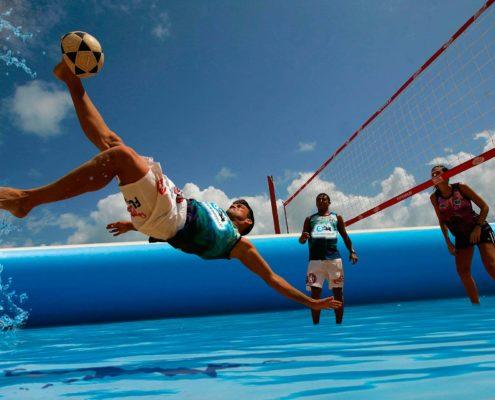 Juagador de waterfootvolley haciendo una tijereta en una piscina deportiva profesional