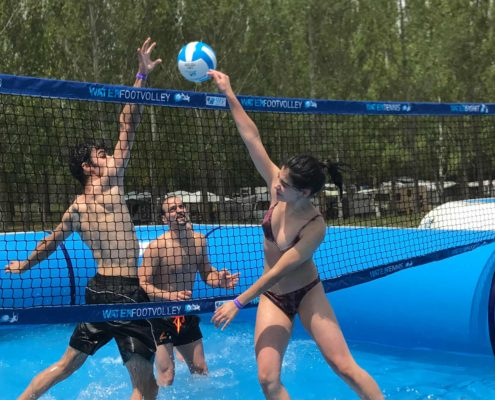 Una jugadora de watervolley remata delante de un bloqueo en una piscina deportiva profesional Watevoley