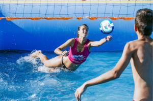 Una jugadora de watervolley Spain® se tira a por un balón en una piscina deportiva profesional Water Sport Pools®