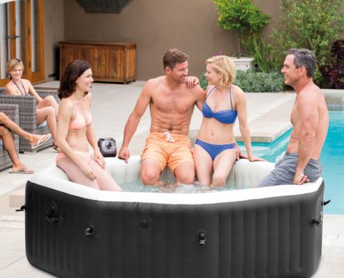 Spa jacuzzy portatil hinchable con 4 personas en su interior al lado de una piscina