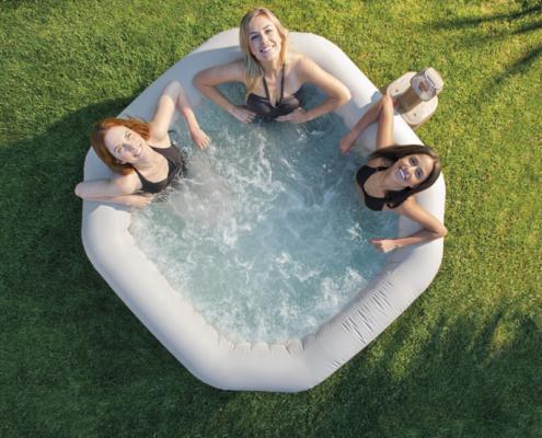 SPA JACUZZY hinchable con tres chicas en su interior situado en un jardín