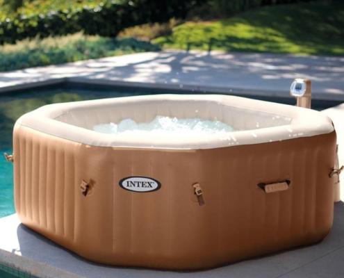 Spa jacuzzy Octogonal portatil hinchable con bomba de calor situado al lado de una piscina