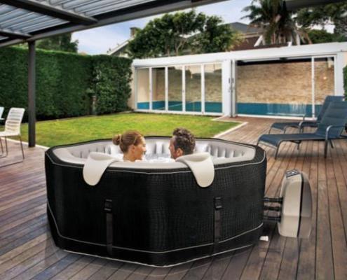 Spa jacuzzy Octogonal portatil hinchable con bomba de calor con una pareja en el interior el jacuzzy situado en una terraza con jardin
