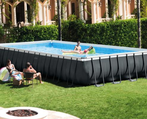 Piscina desmontable para ocio con una pareja en el interior de la misma ella con una colchoneta y el de pie, y en el exterior de la piscina otra pareja sentada en unas sillas