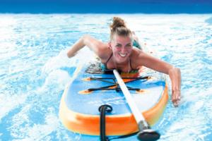 Chica sonriente echada encima de tabla de paddle surf remando con brazos