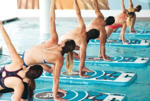 6 personas haciendo yoga sobre tablas en una piscina