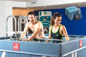 Un hombre haciendo spinning y una mujer en cinta para correr dentro de piscina deportiva