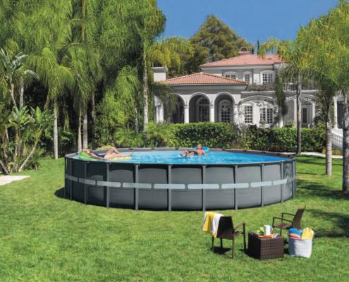 Piscina desmontable redonda con dos personas ella en una colchoneta flotando y el también la piscinas situada en un jardín