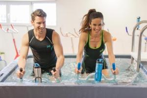 Un hombre y una mujer haciendo spinning con bicicletas adaptadas waterbikes dentro de una piscina deportiva