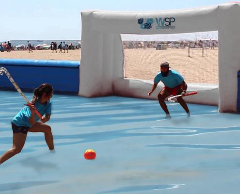 Jugadora al waterhockey golpeando con el steak el balón frente a una portaría
