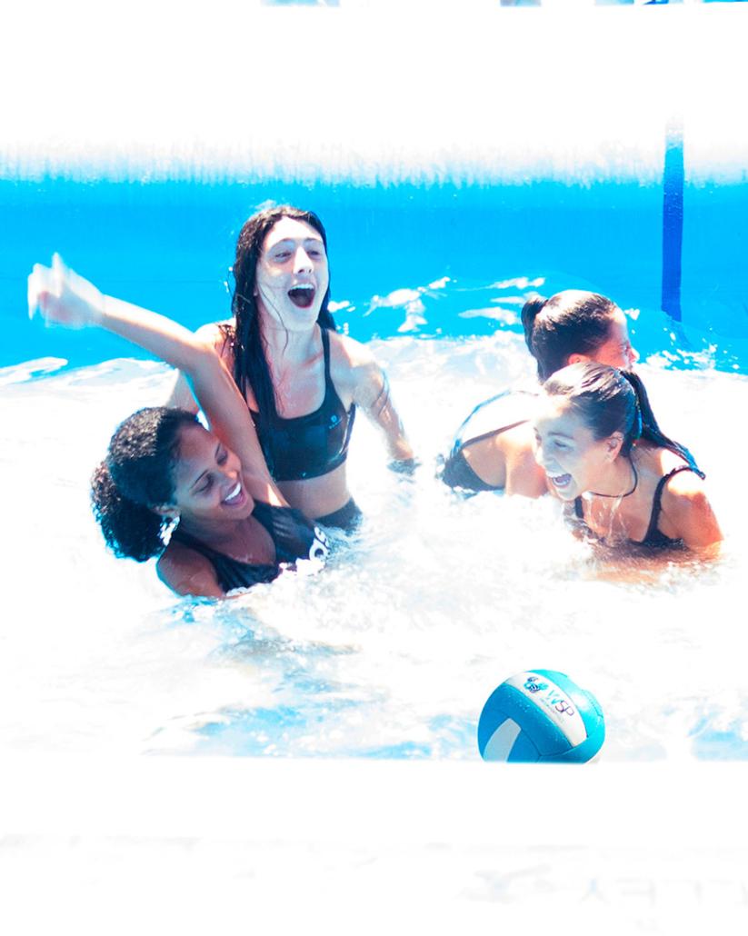 cuatro chicas sonriendo después de un punto disputado dentro de una piscina de watervolley