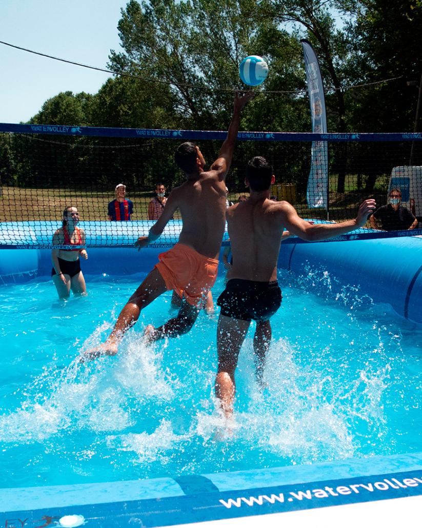 jugadores de watervolley defendiendo en salto en una jugada dentro de una piscina