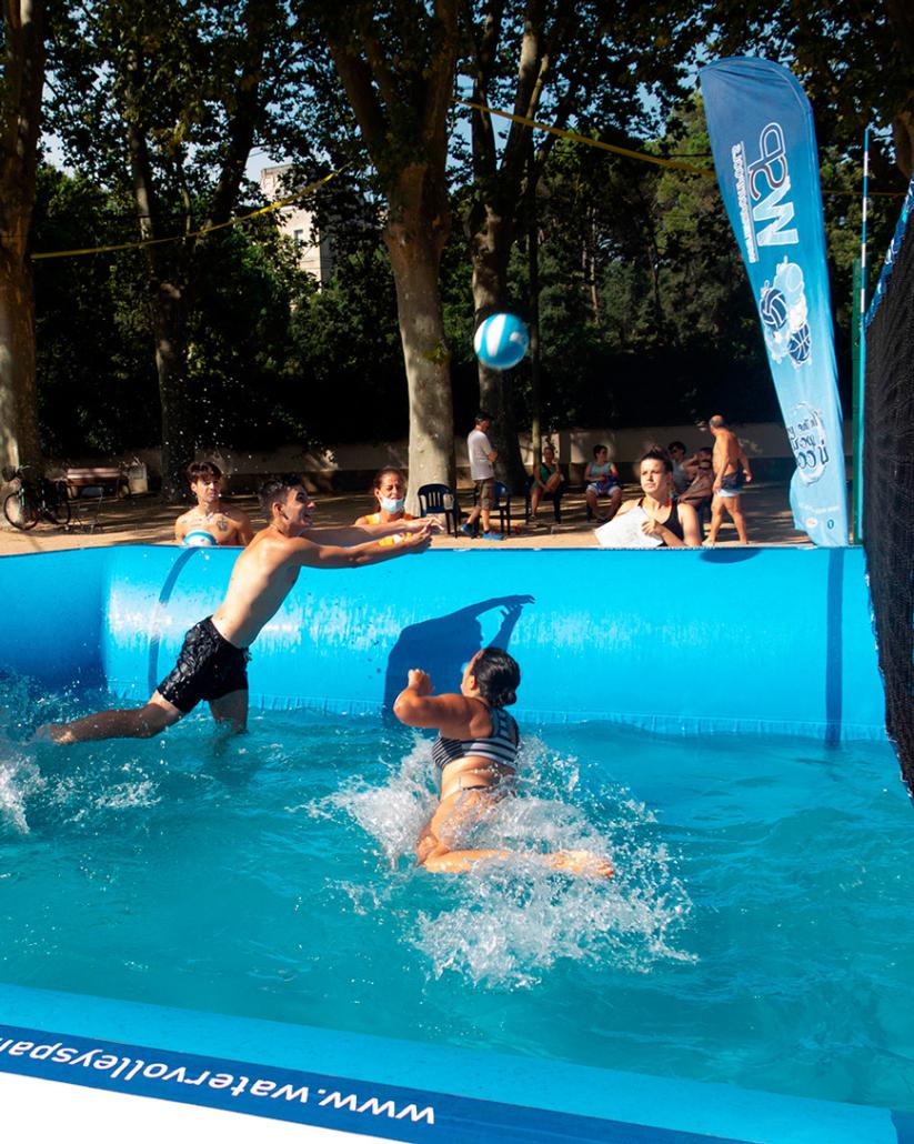 jugadores de watervolley defendiendo en una jugada dentro de una piscina
