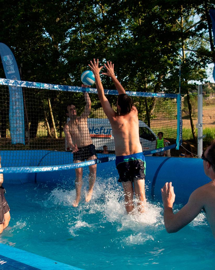 jugadores de watervolley rematando y bloqueando dentro de una piscina