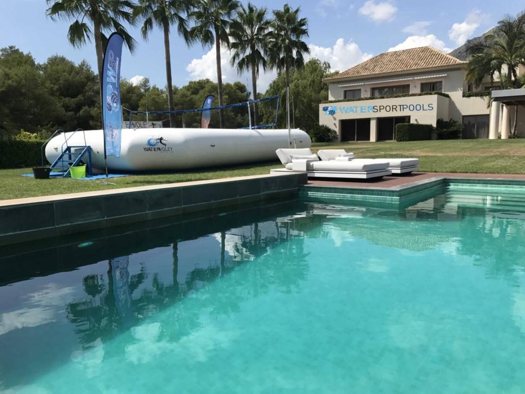 Piscina watersportpools en un jardin al lado de otra pioscina junto a un chalet con palmeras